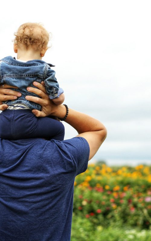 Canva - Baby Sitting on Man's Shoulder